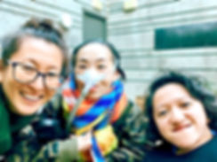 Photo of 3 disabled Asian American women, Mia Mingus, Alice Wong and Sandy Ho (from left to right). Mia is wearing glasses and large hoop earrings. Alice is wearing a brightly colored scarf and an army-camouflage-print jacket. She is wearing a mask over her nose with a tube for her Bi-Pap machine. Sandy has wavy short hair and is wearing a black sweater. Behind them is a concrete wall with a door.