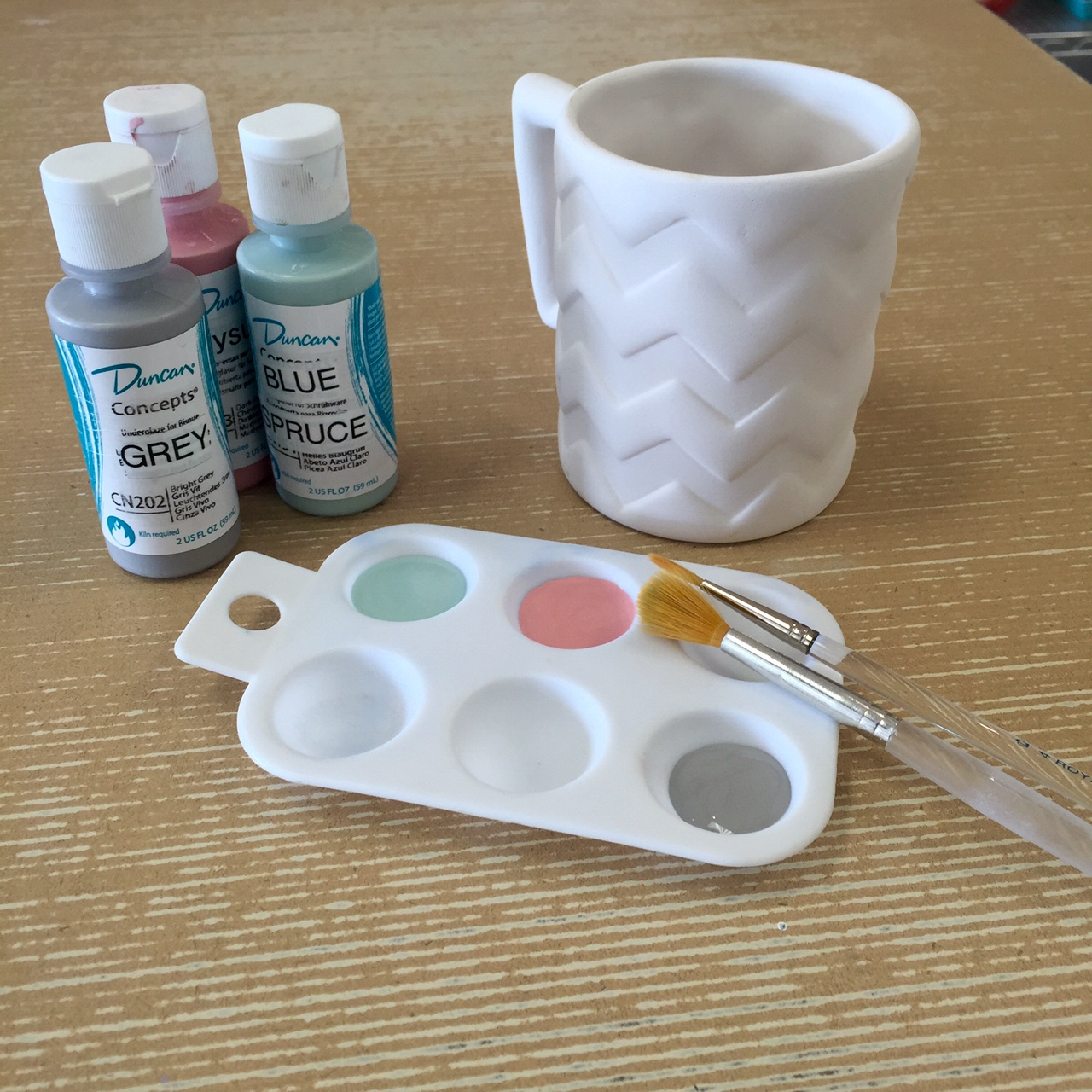 mug with paint and brushes marketing photo