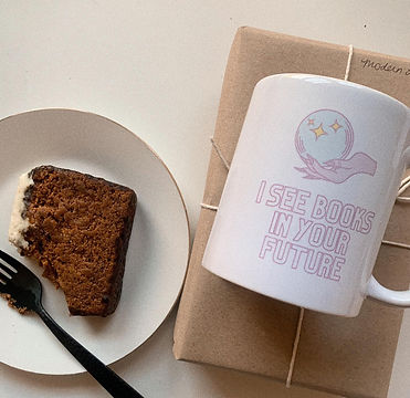 A plate of eaten pumpkin bread next to a wrapped book and a mug.