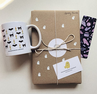 A wrapped book in the middle of the image next to a mug and a bookmark