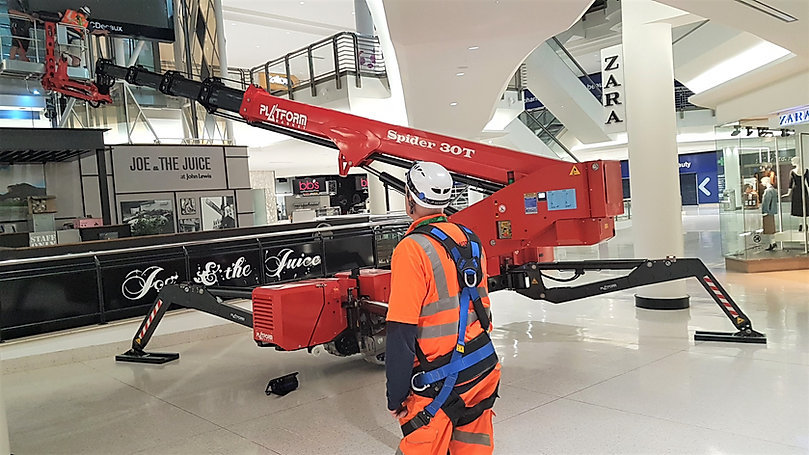 Platform Basket Spider 30T being used inside a shopping centre to install point of sale retail merchandising. The  Spider Lift has extremely low ground pressure and is set-up on decorative flooring tiles without causing damage.