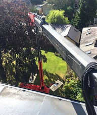 Platform Basket Tracked Spider Lift 33.15 for Hire is set-up in a residential garden for roof access