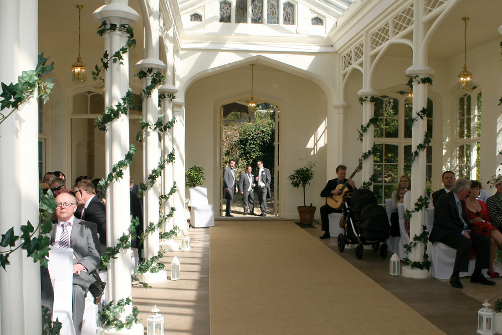 Wedding Guitarist plays pre-ceremony music while groom waits