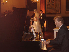 Pianist paying at wedding wit bride and groom in background