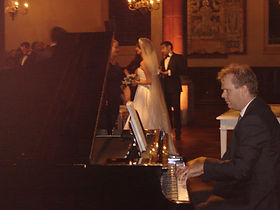 Wedding pianist playing jazz piano  with bride and groom behind