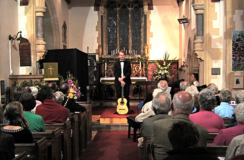 Classical Guitarist talking to audience at church concert