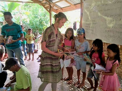 louise-giving-books-children-greenclass.jpg