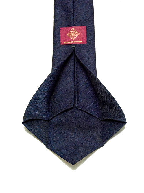 Dark navy herringbone handrolled 7-fold tie made of wool woven in the UK