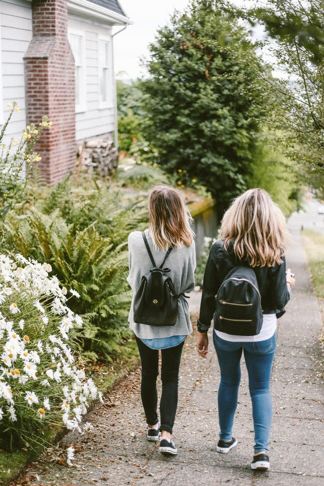 Two girls walking wearing backpacks