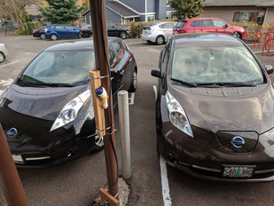 Two of the Community's Electric Vehicles (EVs) in Front of the Onsite Charging Station Powered by Solar Energy with Dedicated EV Parking.