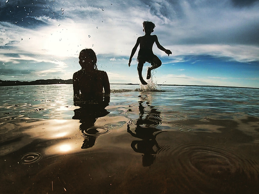 Makai jumping out of the water during a Caribbean sunset while swimming with his mother