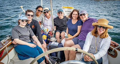 A group photo of family and friends with their loved one, while aboard the sailboat.