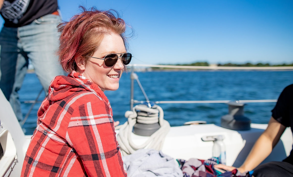 Lady smiling while sitting aboard a sailboat, looking out into the ocean.
