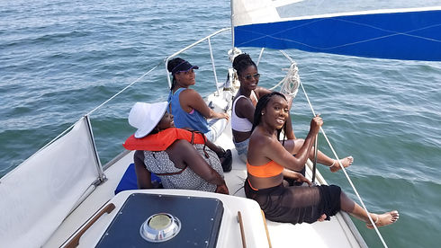A photo of family and friends sitting on the bow of the sailboat during their sail.