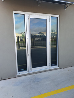 Clear anodized commercial door with vertical windows either side