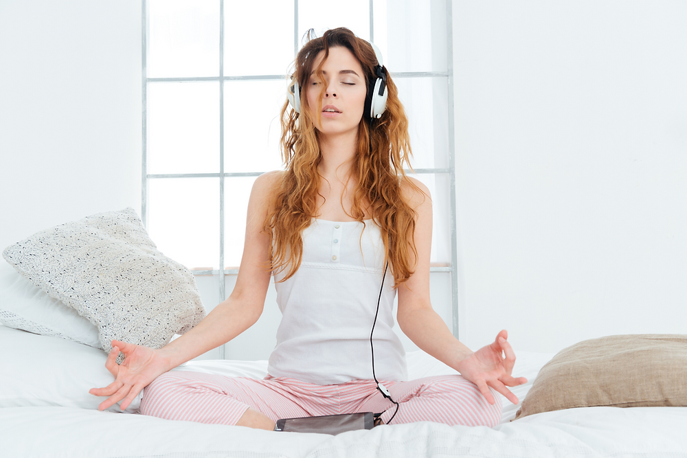 Young woman meditating on her bed with headphones.