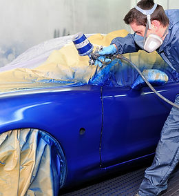 Worker painting a car in a paint booth,.