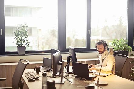man-with-headphones-facing-computer-moni