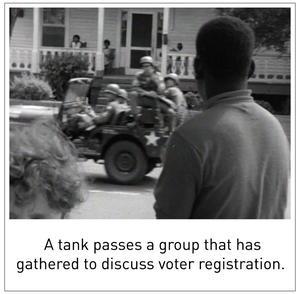 A tank passes a group that has gathered to discuss voter registration.