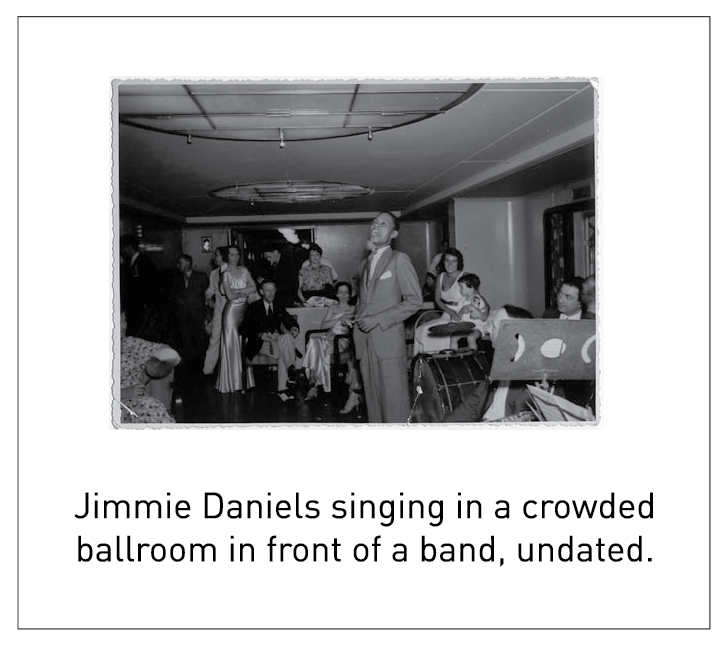 Jimmie Daniels singing in a crowded ballroom in front of a band, undated.