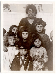 Miss Baharian with group of Kindergarten children, Ellis Island, 1921