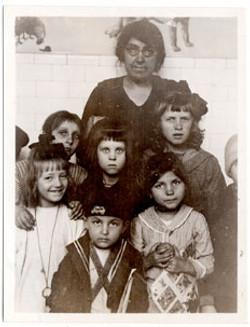 Miss Baharian with group of Kindergarten children, Ellis Island, 1921