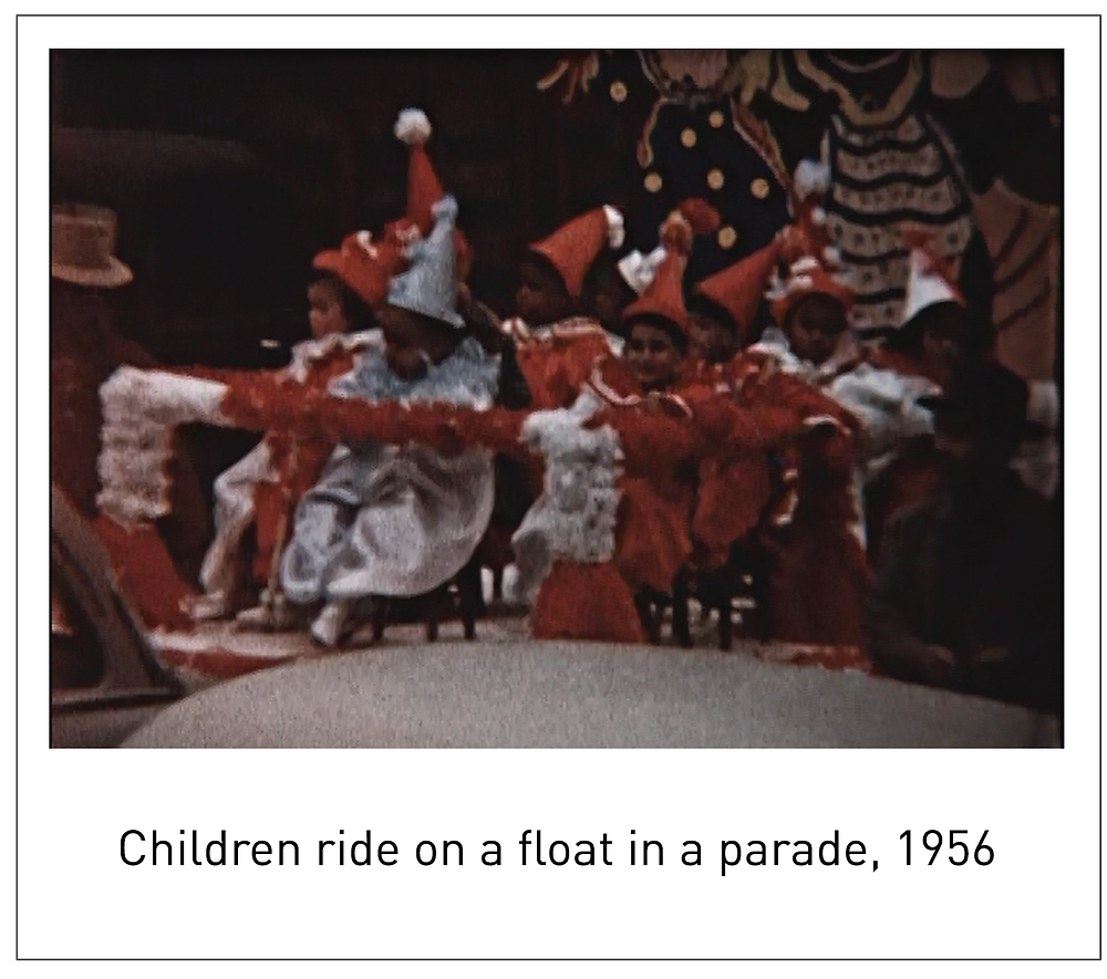 Children ride on a float in a parade, 1956