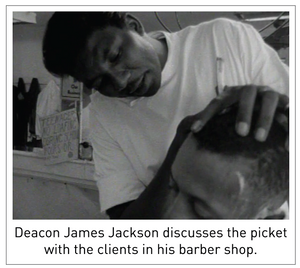 Deacon James Jackson discusses the picket with the clients in his barber shop.