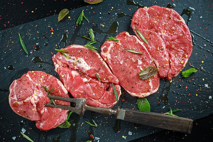 Raw Lamb leg steaks on stone chopping bo