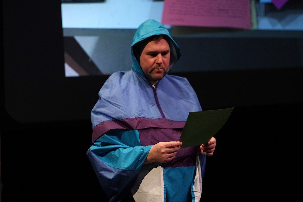 Man in a colourful raincoat reading from a piece of paper.
