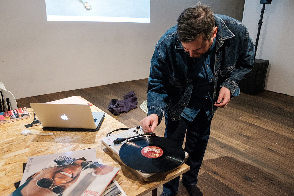 A man in jean jacket putting the needle on a record that sits on a table with some album covers.