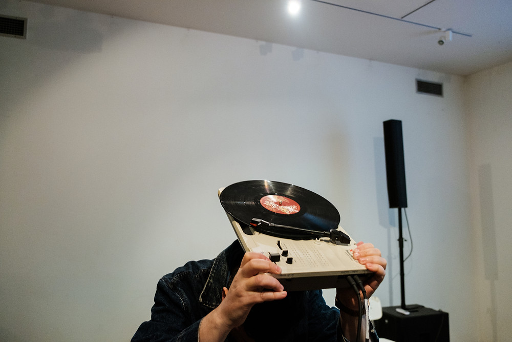 A man covering his head with a turntable.