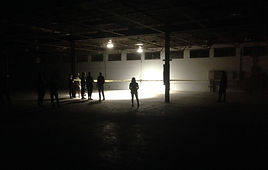 A group of people in a dimly light warehoue standing behin crime scene tape looking at an light open area
