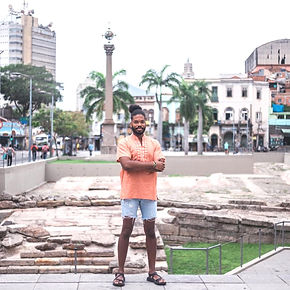 Black man standing with arms crossed at historical site in Rio de Janeiro