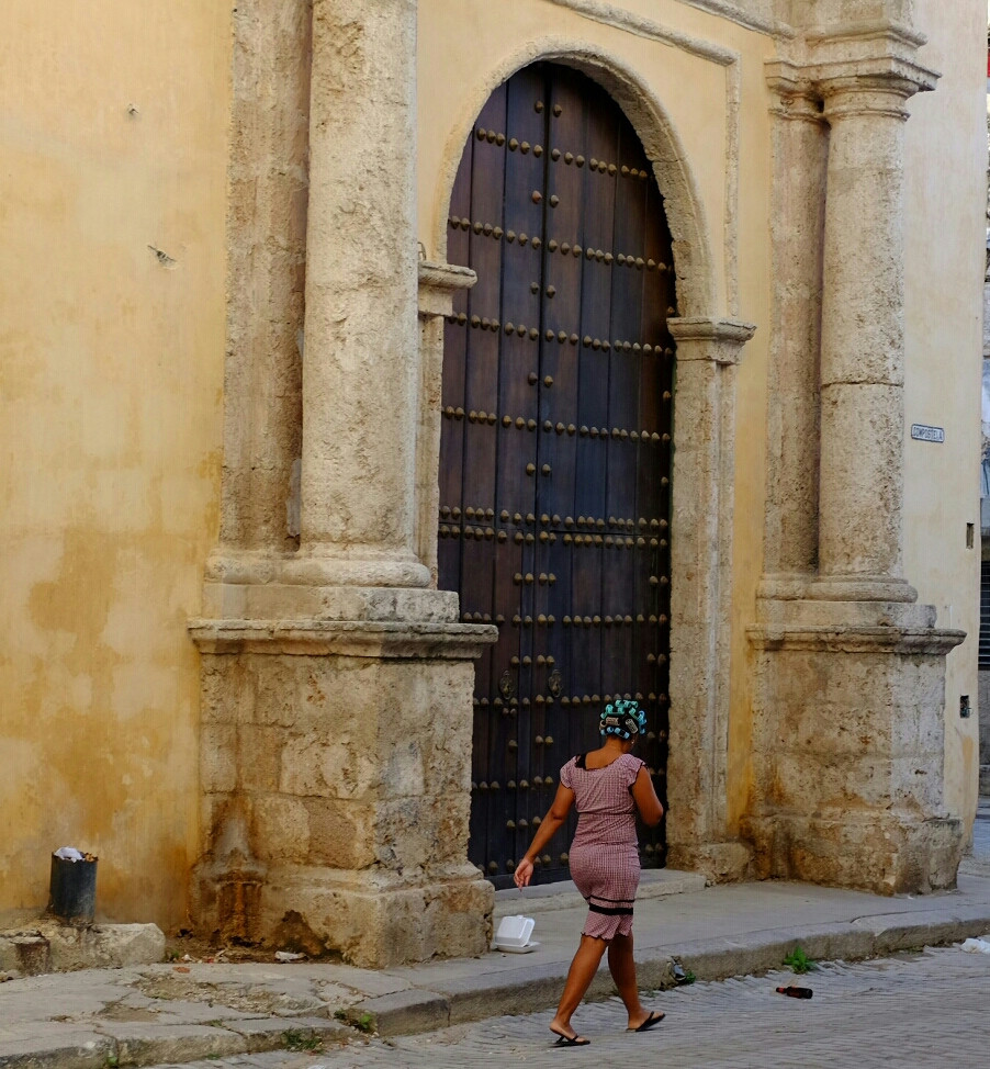 A lady with rollers walks past a old church in Old Havana.