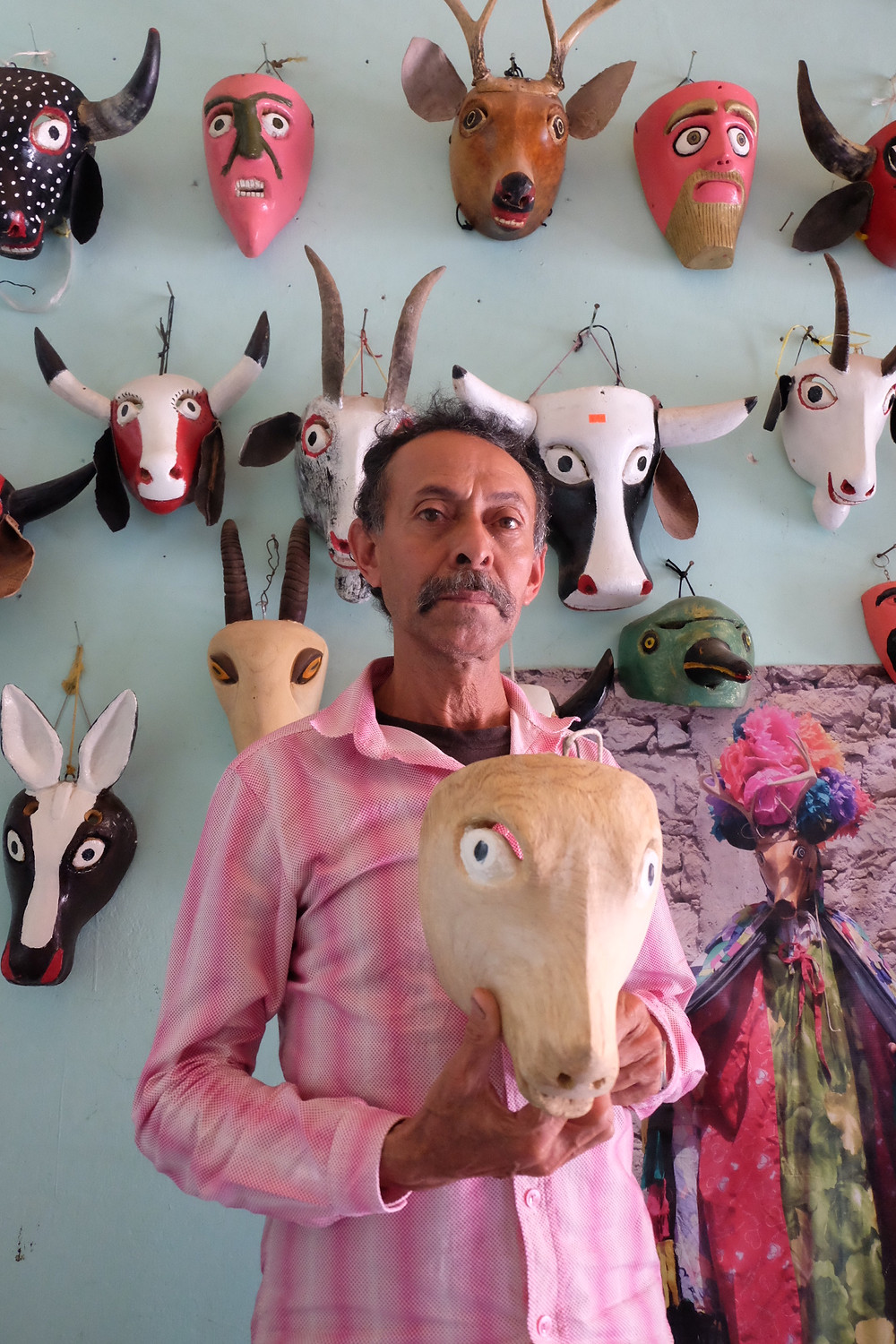 Octavio stands in his home holding a mask that one of his students made, in front of a wall of his own creations.