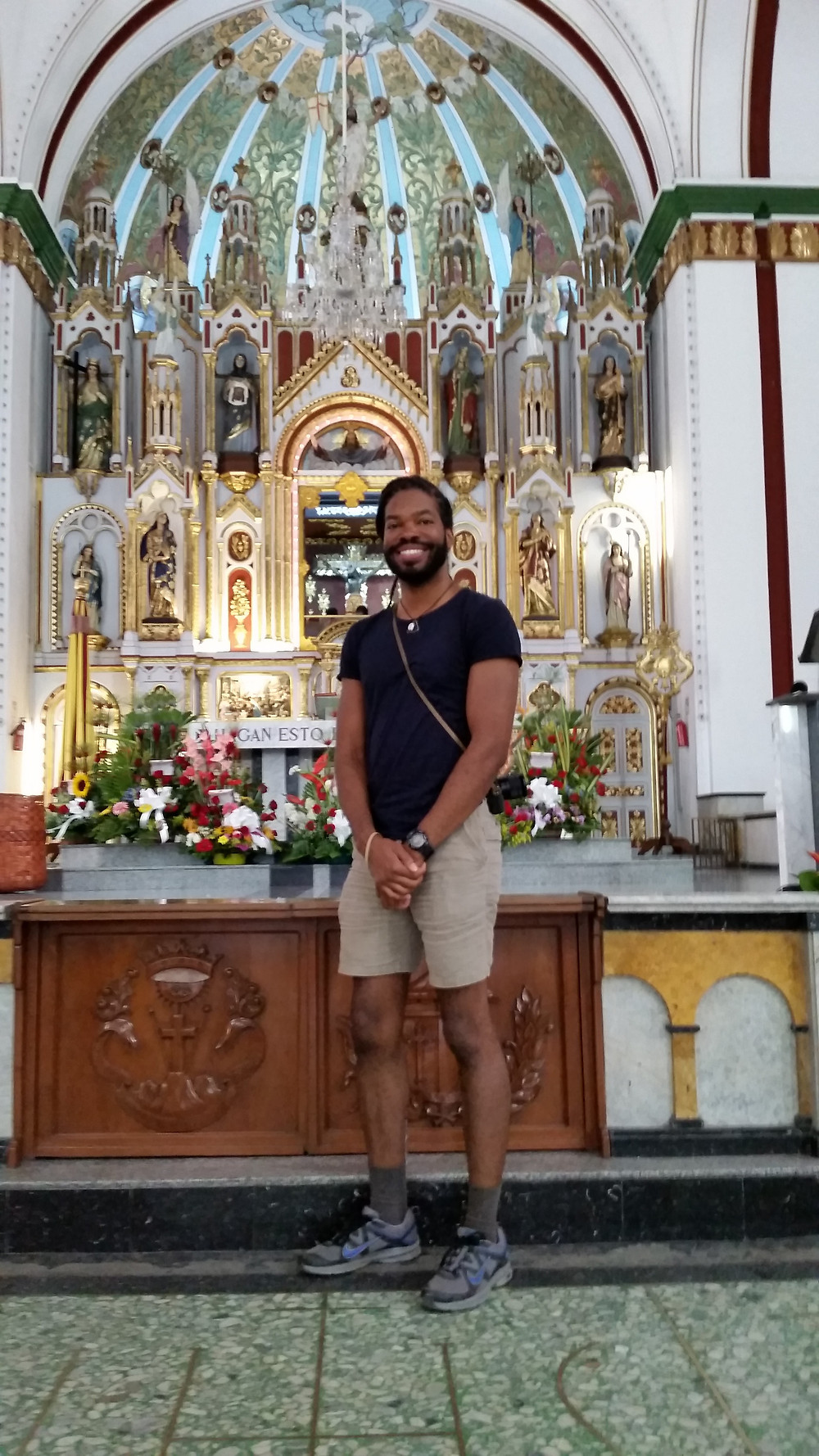 Standing in front of the altar of Black Jesus in Buga, Colombia.