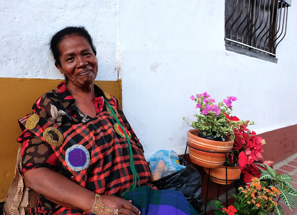 Dora, an Afro-Colombian sells fruits and flowers outside of a convent in the San Antonio section of Cali.