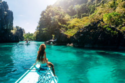 Back view of the young girl relaxing on the boat and looking at the island.jpg Travelling tour in As