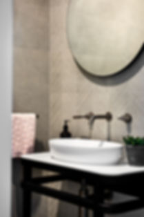 Powder room, round mirror, taps, textured tile