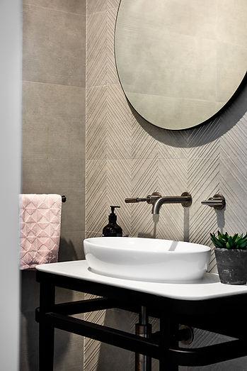 Powder room, round mirror, taps, textured tile