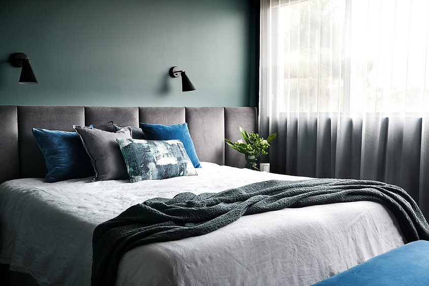 master bedroom with deep green walls, white sheer curtains, plush wall to wall bedhead, coordinated cushions