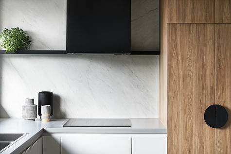 close up of kitchen with matt grey benchtop, marble-look porcelain splashback, timber cabinetry