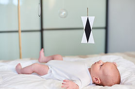 Adorable baby boy in white sunny bedroom