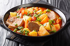 Cooked beef tongue with vegetables in tomato sauce close-up in a bowl on the table..jpg