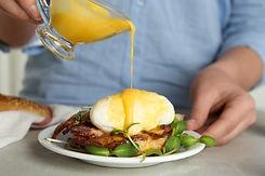 Woman pouring Hollandaise sauce onto egg