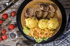 Braised pork tongues in horseradish sauce served with potatoes and salad. Top view..jpg