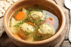 Bowl of Jewish matzoh balls soup on wooden table, closeup.jpg