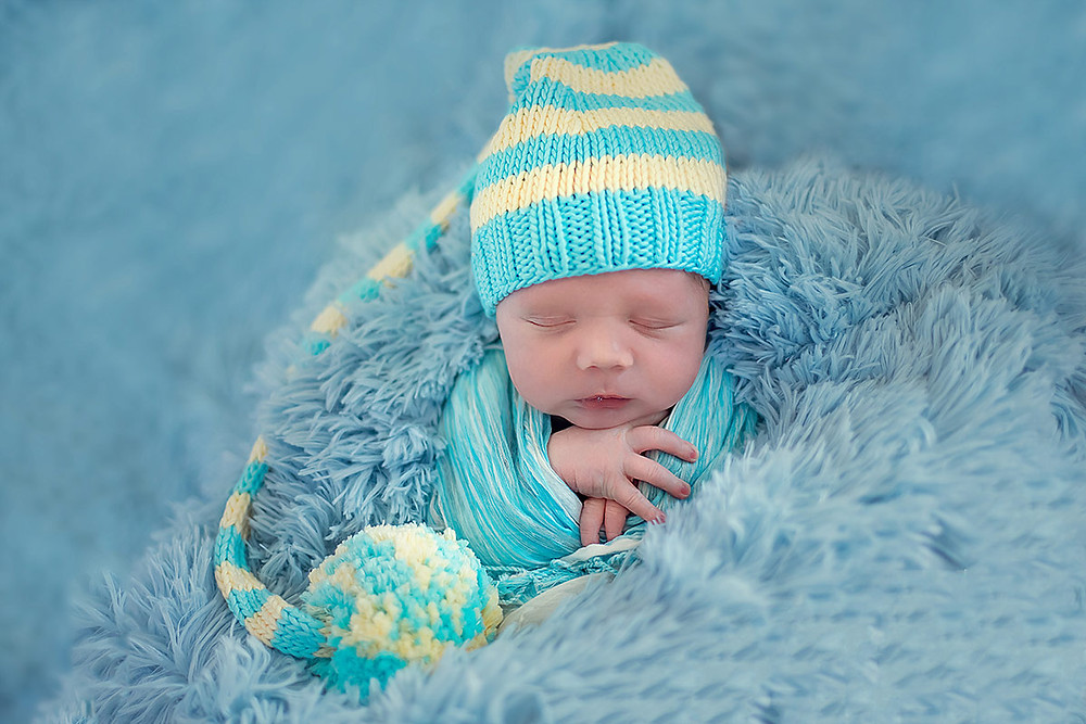 studio portrait of newborn baby boy in blue
