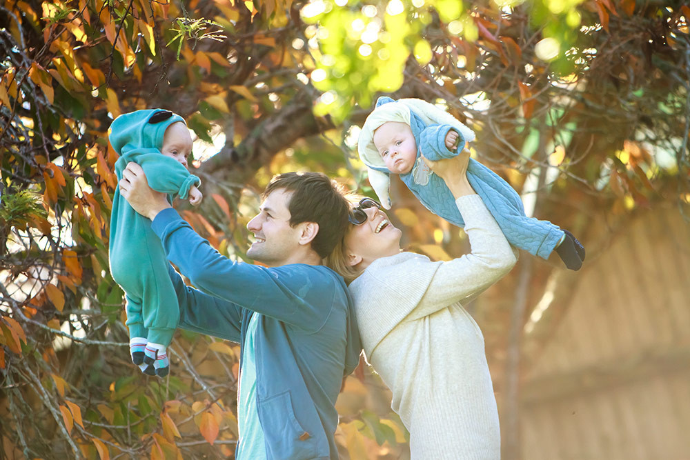 outdoor portrait of young happy family on natural background, family photography